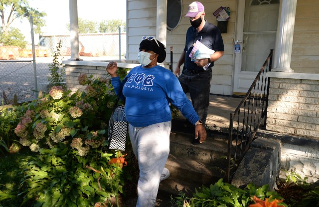 Meko Gray, left, of the Erie Chapter of Zeta Phi Beta Sorority Inc., and Pastor Jim Parkinson of the First Methodist Church, go door-to-door Aug. 8, 2020 on East 19th Street in Erie, handing out masks and literature about COVID-19. The outreach event, organized by United Clergy of Erie, focused on the communities which have experienced high rates of COVID-19.