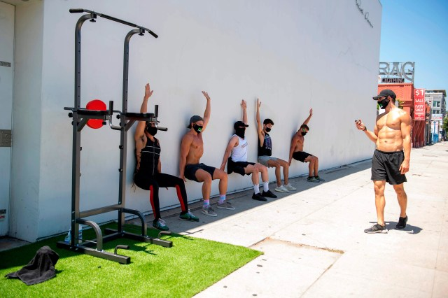 People take an outdoor class at Pylo Fitness, with workout equipment set up on the sidewalk on La Brea Blvd, on Aug. 7 2020, in Los Angeles, California, amid the novel coronavirus pandemic.