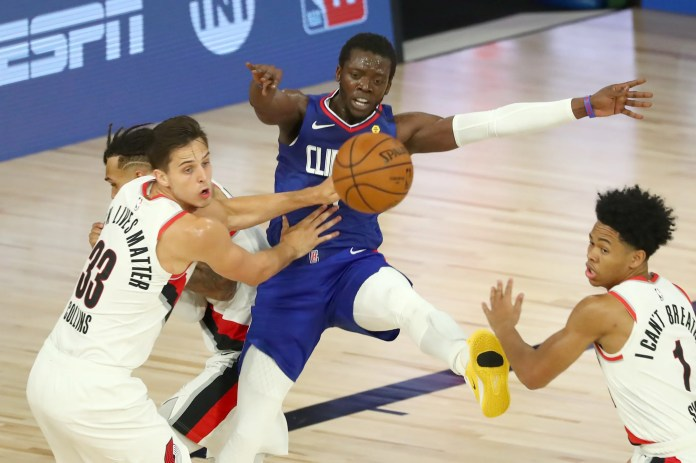 Aug. 8: Clippers guard Reggie Jackson (1) loses control of the ball between Blazers defenders Zach Collins (33) and Anfernee Simons (1).