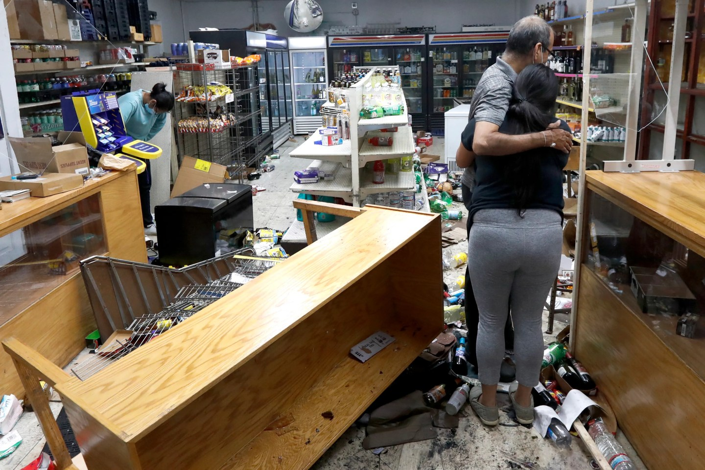 Yogi Dalal hugs his daughter Jigisha as his other daughter Kajal, left, bows her head at the family food and liquor store Monday, Aug. 10, 2020, after the family business was vandalized in Chicago.
