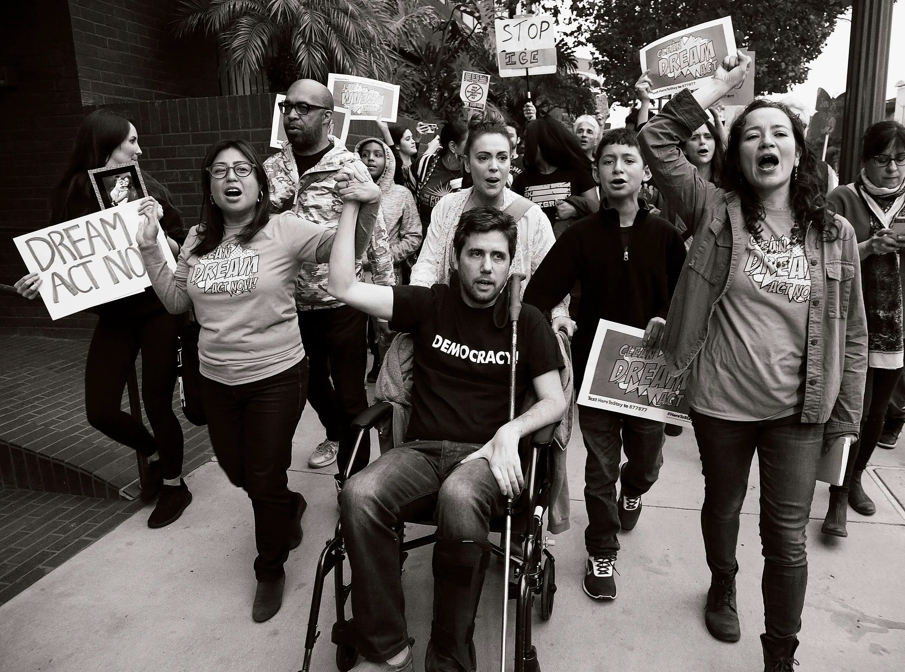 Cristina Jiménez Moreta, left, and Ady Barkan, in wheelchair, lead a small delegation to the office of California Democratic Sen. Dianne Feinstein, urging the Democrats to protect the Deferred Action for Childhood Arrivals (DACA) program in Los Angeles,  Jan. 3, 2018.