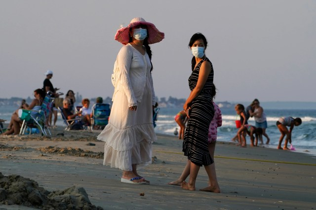 In this Aug. 11, 2020, file photo, women wear masks to help prevent the spread of coronavirus at the end of a beach day in Ogunquit, Maine.