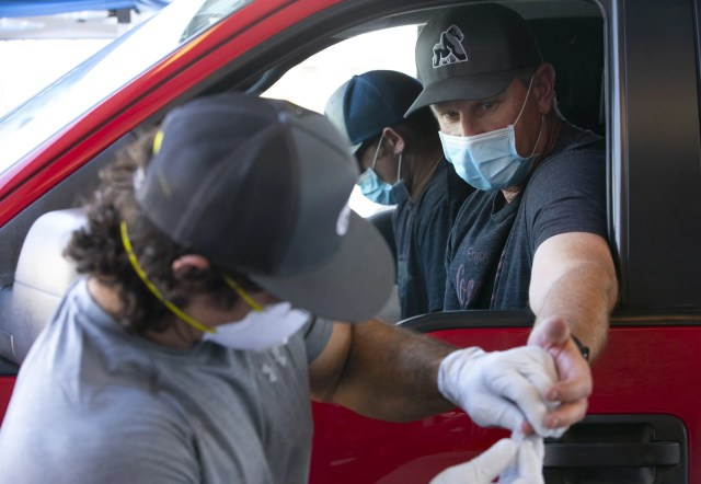 Phoenix Fire Department battalion chief Scott McDonald (right) receives a free antibody test for the new coronavirus, administered by Phoenix firefighter paramedic Nate Byrd at the Phoenix Fire Department training facility in Phoenix on April 28, 2020.