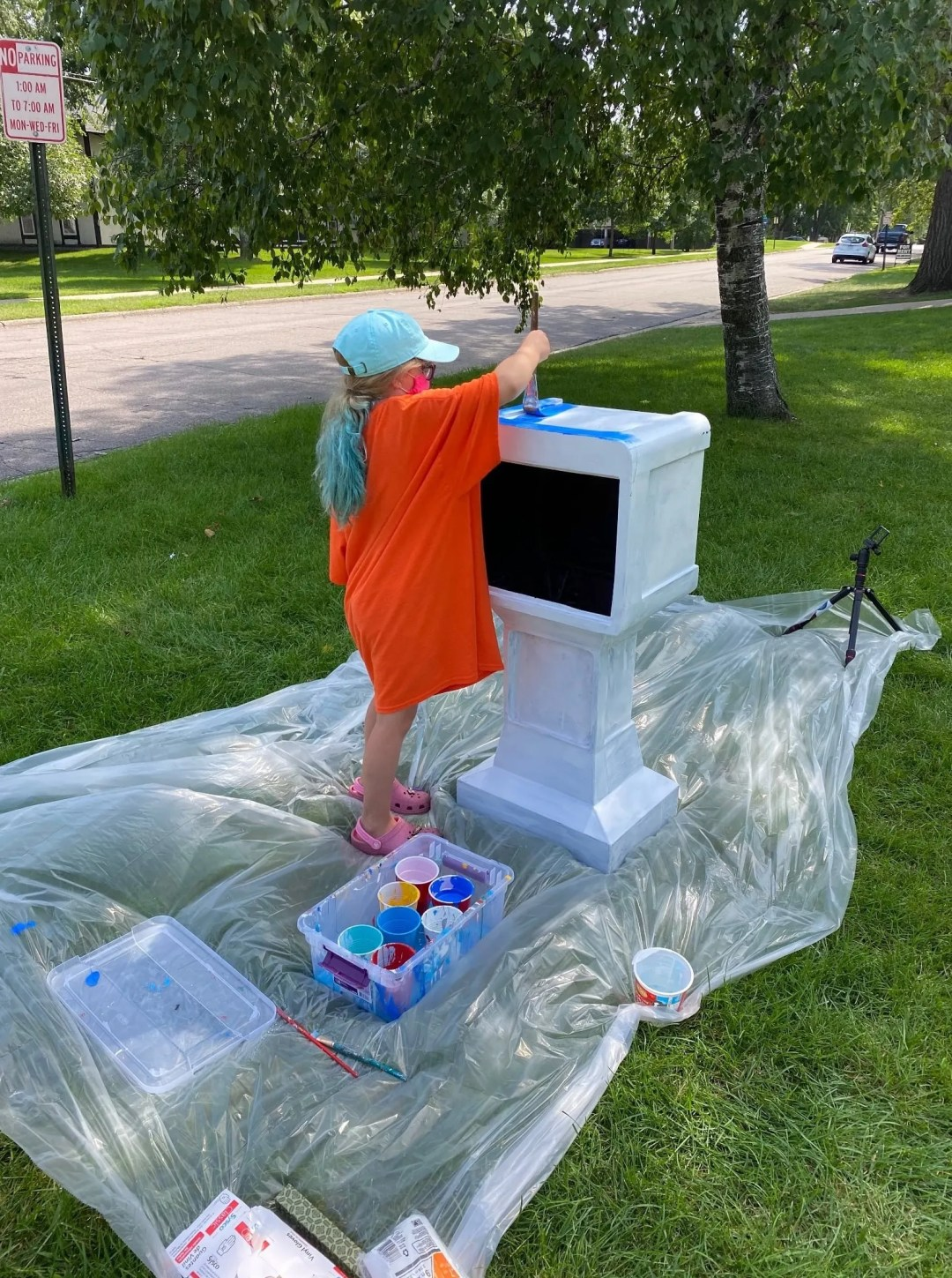 Local artist Adam Spaeth and his daughter Zoe work together to paint a STEM distribution box at the COP House in St. Cloud.