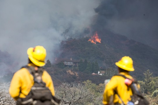 Firefighter watch as a wildfire burns at a hillside behind homes in Yucaipa, Calif., Saturday, Sept. 5, 2020. (AP Photo/Ringo H.W. Chiu)