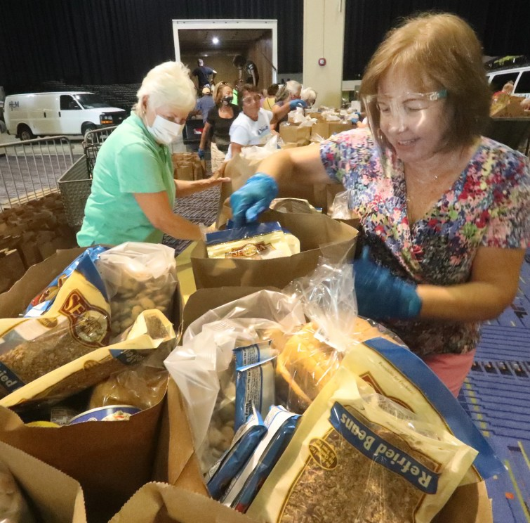 Volunteer Candance Stewart, at right, an army of other volunteers, fill bags with food for Halifax Urban Ministries, Tuesday September 8, 2020 inside the Ocean Center.