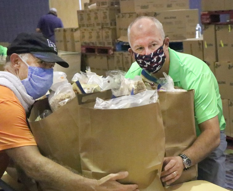Halifax Urban Ministries Executive Director Buck James, at right, joins the army of volunteers filling bags with food for Halifax Urban Ministries, Tuesday September 8, 2020 inside the Ocean Center.