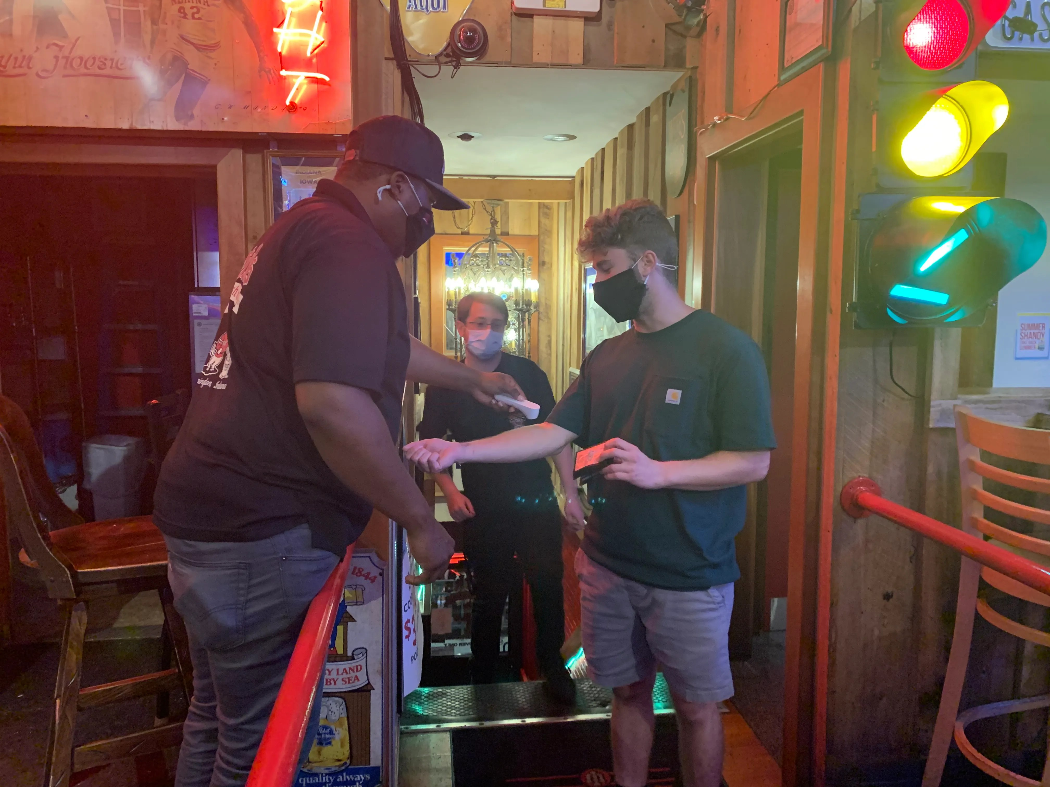 A bouncer tends to a patron entering Nick's bar near the Indiana University campus on Thursday.