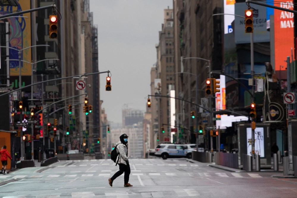 A man wearing a mask crosses the street in a quiet Times Square.