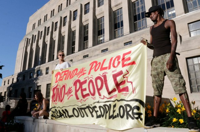 Protesters hold a banner wanting to defund police and then fund people during the protest against ICE, Friday, July 10, 2020, in Sheboygan, Wis.