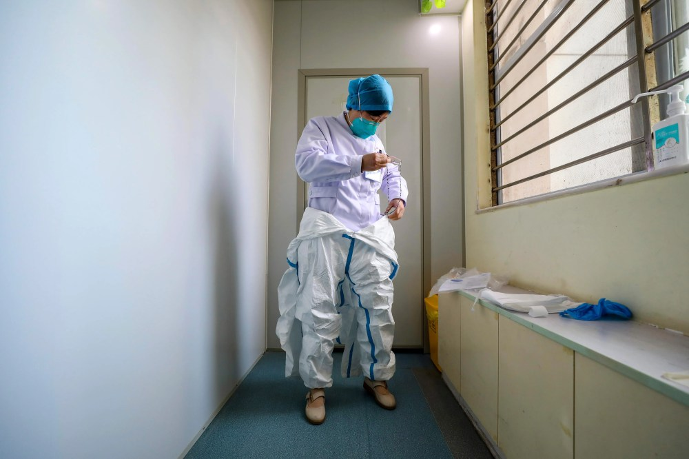 A doctor puts on a protective suit at a hospital in Wuhan.