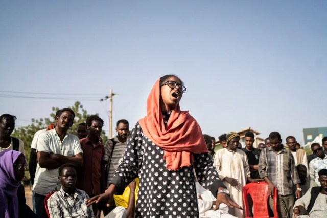 A young woman addresses a crowd that has gathered ahead of the protests calling for an end to the military junta on April 27, 2019 in Khartoum, Sudan.
