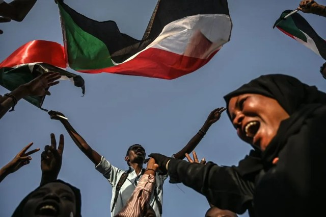 Sudanese protesters chant slogans and wave the national flag during a sit-in outside the army headquarters in the capital Khartoum on April 30, 2019. - Sudanese protesters called for a mass rally, insisting the army is not serious about handing power to civilians nearly three weeks after it toppled autocratic president Omar al-Bashir.