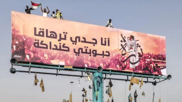 A picture taken during anti-regime protests on April 11, 2019 shows a huge billboard bearing an image of Alaa Salah, a Sudanese woman propelled to internet fame after clips went viral of her leading powerful protest chants against Sudan's president, in the Sudanese capital Khartoum. Arabic writing next to her photo in a white gown reads: