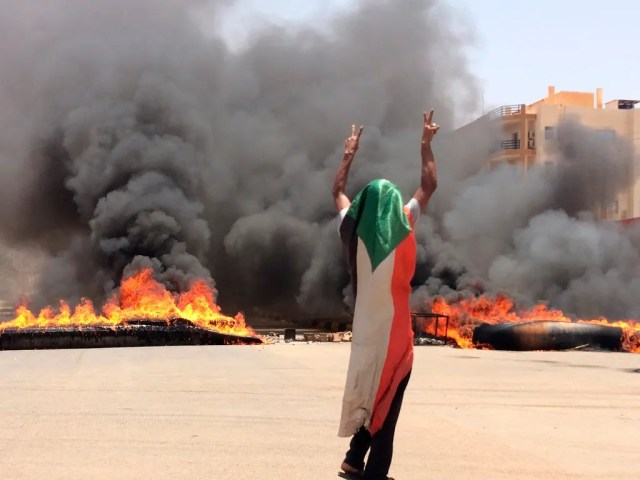 In this June 3, 2019 file photo, a protester wearing a Sudanese flag flashes the victory sign in front of burning tires and debris, near Khartoum's army headquarters, in Khartoum, Sudan. SudanÕs uprising has ushered in a new era both for the nation and for Sudanese women after three decades of autocratic rule by Omar al-Bashir. Sudanese women played a pivotal role in the protests that brought down al-Bashir, and under a joint military-civilian council in power now, they hope for more freedom and equality, and seek to overturn many of the restrictive Islamic laws from the previous era.