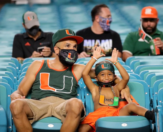 Armando Espinoza and his son Armando 3, of Belle Glade, watch as the University of Miami hosts the UAB Blazers at Hard Rock Stadium.