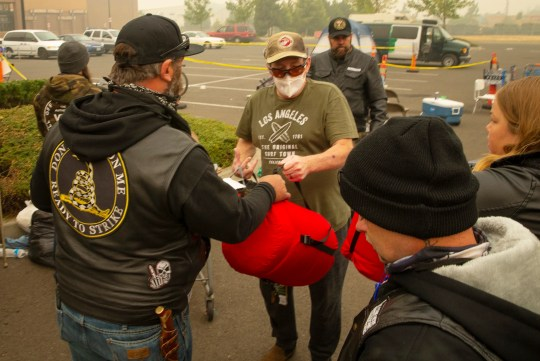"""Ron Haynes, center, is surrounded by volunteers offering supplies at a makeshift donation center set up in a Walmart parking lot in South Medford, Ore. Sept. 12, 2020. Haynes does not know if his home survived. His wife had a stroke earlier this year and is suffering from lung cancer as well. """"She can't be out in this smoke,"""" said Haynes as he gathered up supplies. The pair had been staying in a motel the last few days."""