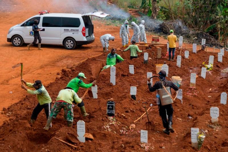 Des travailleurs creusent des trous sur un site funéraire pour les victimes du COVID-19 à Jakarta, en Indonésie, le 11 septembre 2020. La capitale indonésienne prévoyait de réimposer un verrouillage partiel dès le 14 septembre par crainte d'une augmentation des cas de coronavirus.