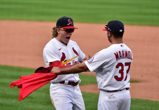 St. Louis Cardinals center fielder Harrison Bader celebrates with bench coach Oliver Marmol (37) after the team defeated the Milwaukee Brewers to clinch a postseason spot.