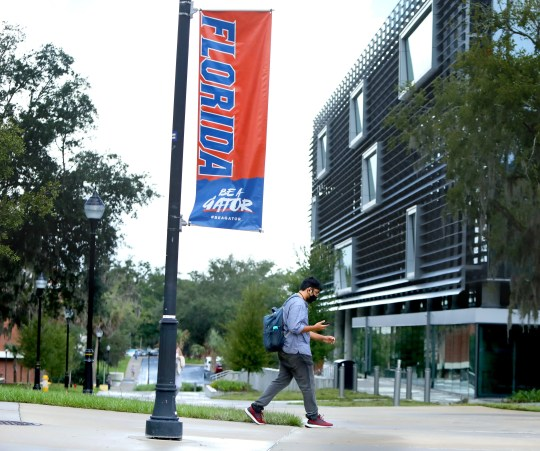 A student walks past a sign at the University of Florida as the first day of classes begin on Aug. 31. Gov. Ron DeSantis thinks some university policies go too far in disciplining students for socializing amid the pandemic.