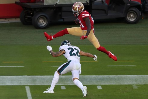 San Francisco 49ers wide receiver Brandon Aiyuk, top, jumps over Philadelphia Eagles safety Marcus Epps (22) to score on a touchdown run during the first half of an NFL football game in Santa Clara, Calif., Sunday, Oct. 4, 2020.