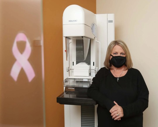 Cindy McDonald of New Franklin stands next to the mammography unit before her annual mammogram at Reflections Breast Center at Cleveland Clinic Akron General Friday, Oct. 16, 2020 in Akron, Ohio.