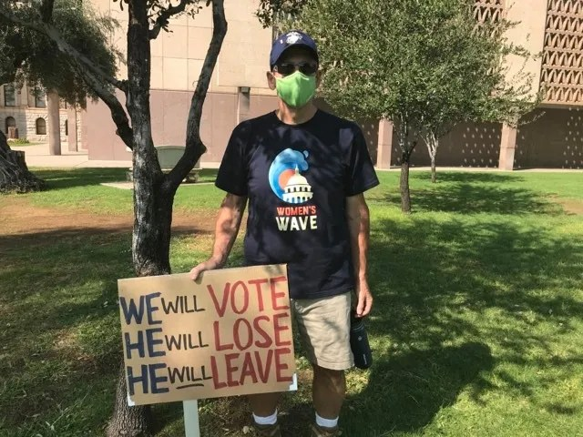Mike Ostermeyer holds up his sign opposing President Donald Trump while at the Arizona Capitol lawn on Oct. 17, 2020.