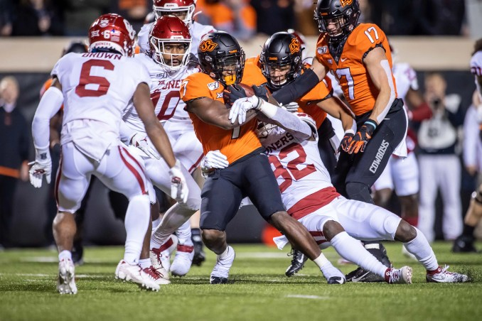 Oklahoma State running back LD Brown (7) is tackled by Oklahoma safety Delarrin Turner-Yell during their 2019 game at Boone Pickens Stadium.