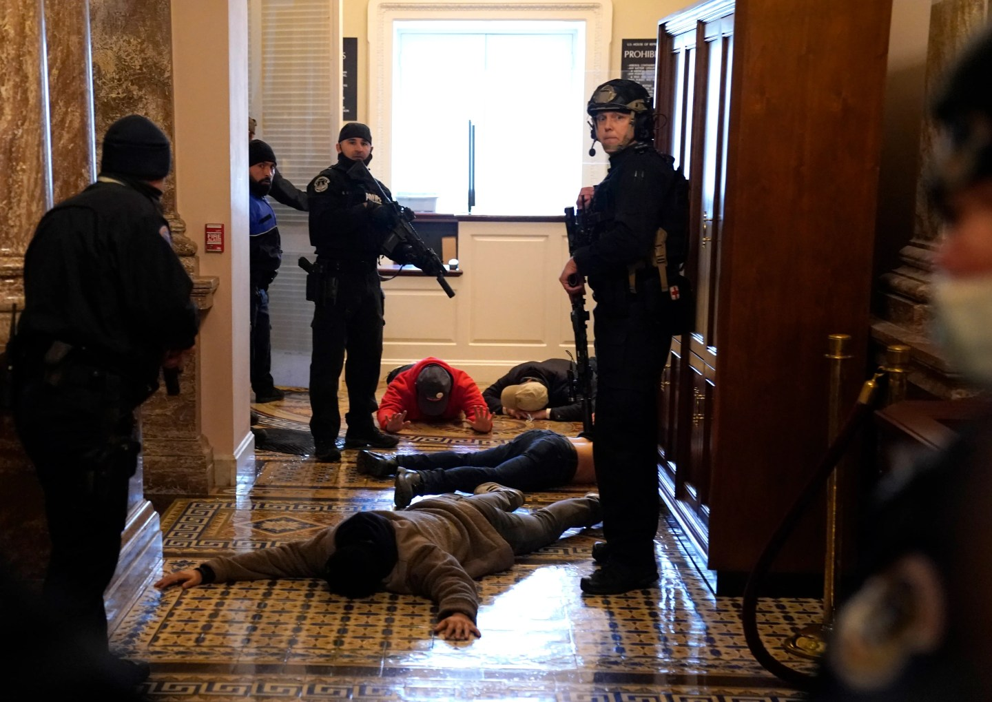 U.S. Capitol Police detain protesters at gunpoint outside of the House chamber, where a joint session of Congress had been meeting Jan. 6 to confirm the votes of the Electoral College.