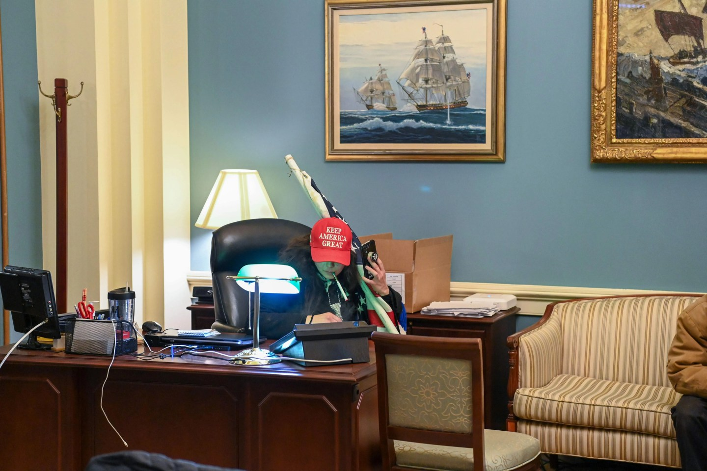 A supporter of President Donald Trump holding an American flag sits at a desk after invading the Capitol on Jan. 6 in Washington. Some wrote menacing notes in lawmakers' offices and smoked after breaking in.