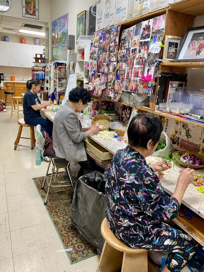 Women string flower garlands at Cindy's Lei Shoppe, in Honolulu's Chinatown. Cindy, who founded the store more than 60 years ago, sits in the middle.