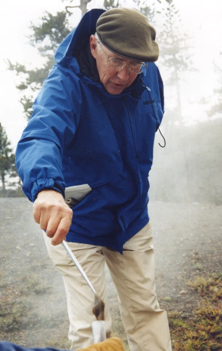 Tom Brock collects a sample from a hot spring in Yellowstone National Park in 1995.  A pioneer in his field, Brock's discovery of bacteria that can live in extremely high temperatures led to major advancements in biology and medicine, including the technology that is used in COVID-19 PCR tests.