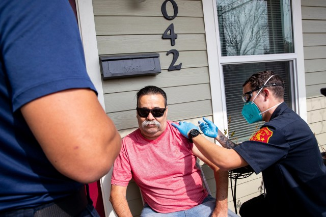 Corpus Christi firefighter cadet Marcus Maldonado gives Samuel Sanchez a COVID-19 vaccine outside this home during the first day of the Senior Vaccination Program in Corpus Christi, Texas on Jan. 26, 2021.