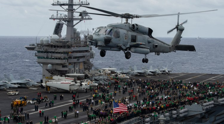 """An MH-60R Sea Hawk helicopter, from the """"Battlecats"""" of Helicopter Maritime Strike Squadron (HSM) 73, hovers above the flight deck of the aircraft carrier USS Nimitz during an air power demonstration Monday. The Nimitz and its crew have been away from families back home for more than 320 days."""