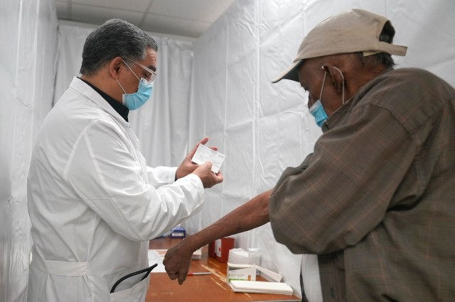 Dr. Victor Peralta, left, examines Sundar Surujmohan's vaccination card before giving him his second dose of COVID-19 vaccine in New York City on Feb. 5.