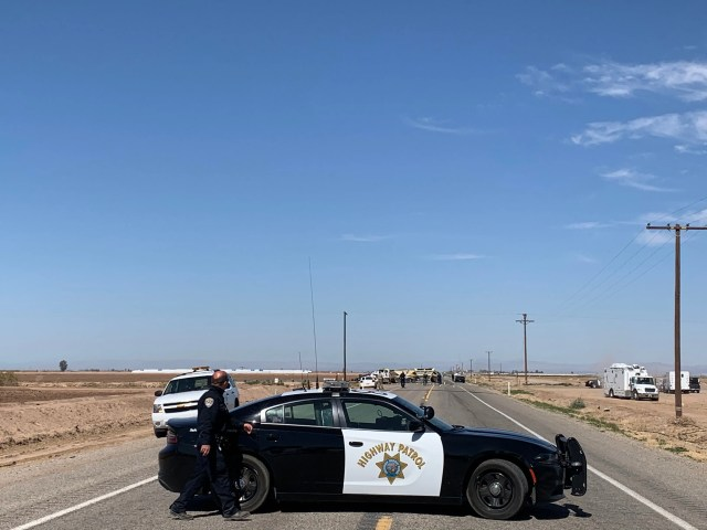 Police pushed reporters back from the scene on the side of Highway 115 near Holtville, Ca., as investigators scan the area from the sky, March 2, 2021.