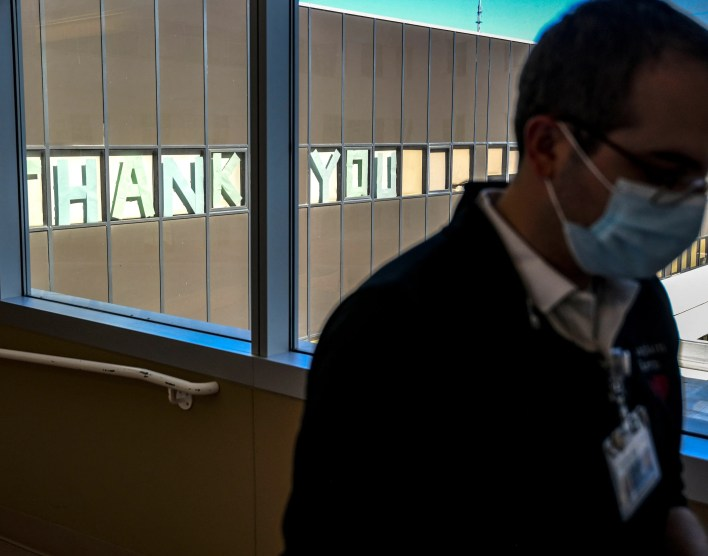 Each day at Providence Holy Cross Medical Center in Los Angeles, Chaplin Kevin Deegan passes through a hallway filled with glass windows to get to the COVID unit, as he does pictured on Friday, Feb. 12, 2021. Outside the windows is a message thanking hospital staff for their work.