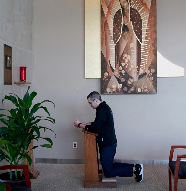 Chaplain Kevin Deegan prays while inside the Providence Holy Cross Medical Center chapel on Friday, Feb. 12, 2021, in Los Angeles.