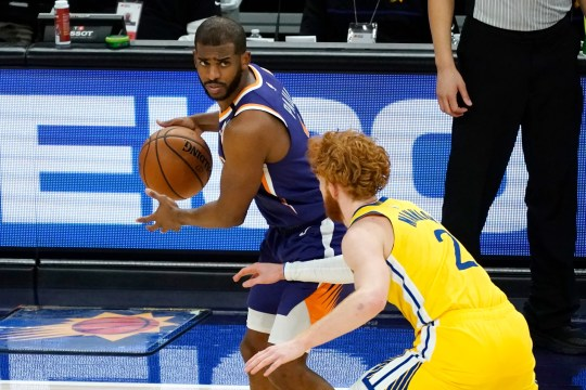 Phoenix Suns guard Chris Paul is defended by Golden State Warriors guard Nico Mannion during the second half of an NBA basketball game Thursday, March 4, 2021, in Phoenix. (AP Photo/Rick Scuteri).