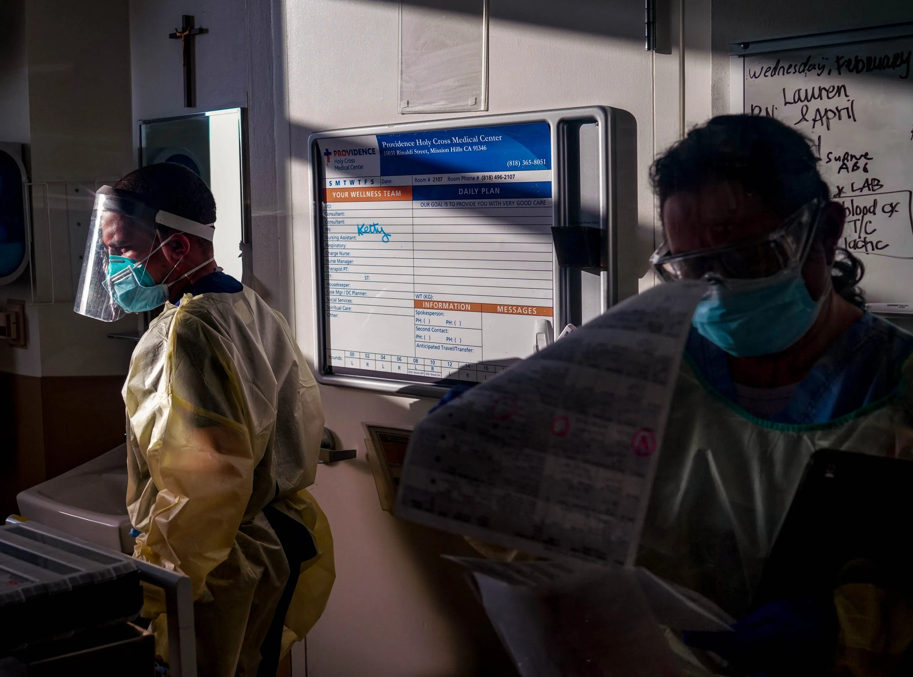 Jacques Coupet, left, a dialysis registered nurse, looks at a patient receiving dialysis treatment while medical staff attends to a patient on Wednesday, Feb. 10, 2021, in the intensive care unit at Providence Holy Cross Medical Center in Los Angeles.