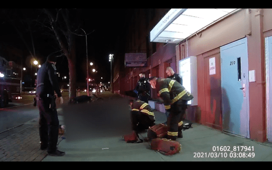 Rochester police officers and firefighters try to render aid to a man outside the Open Door Mission on West Main Street after an officer shot the man who was armed with a knife in this screenshot from body-worn camera footage. (March 10, 2021)