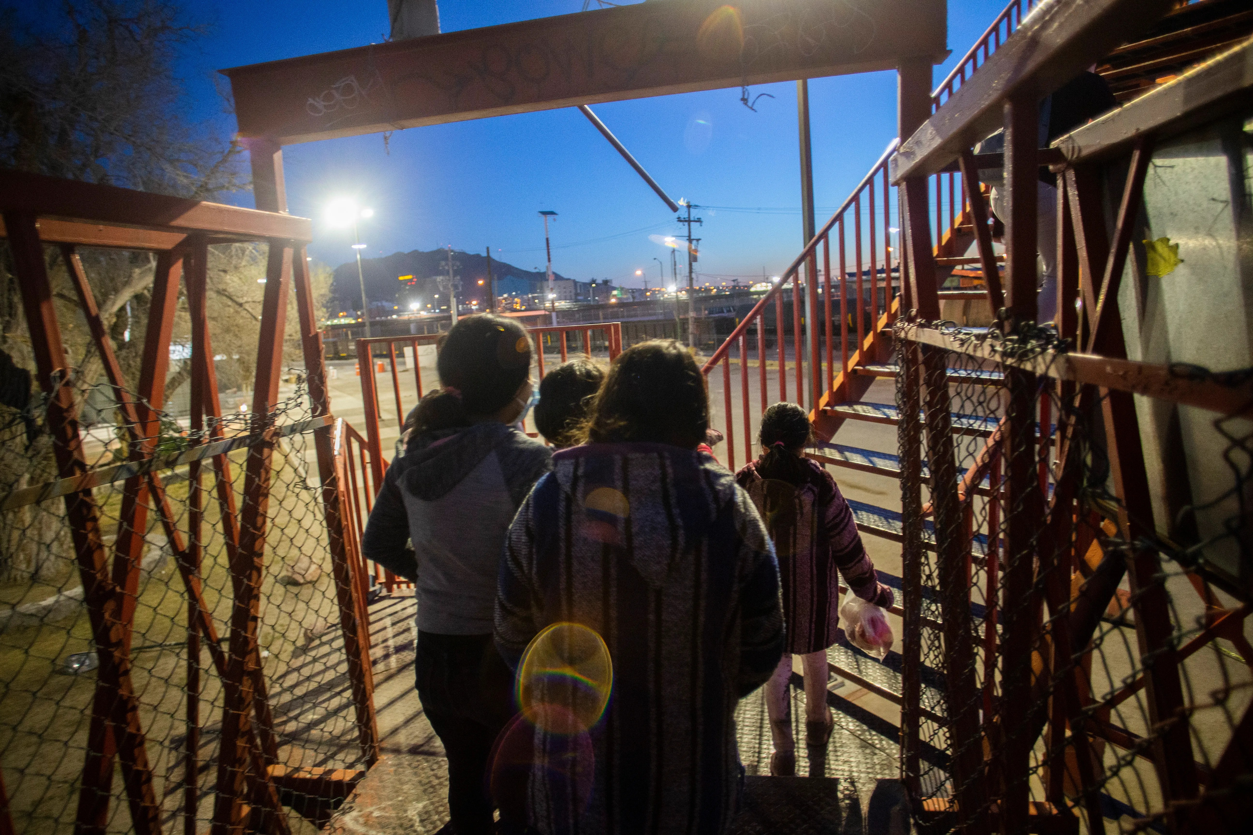 Children and women cross a pedestrian bridge in Juarez, Mexico, on March 11 after being returned to Mexico from the USA. Advocates say this is when immigrants are particularly vulnerable to danger.