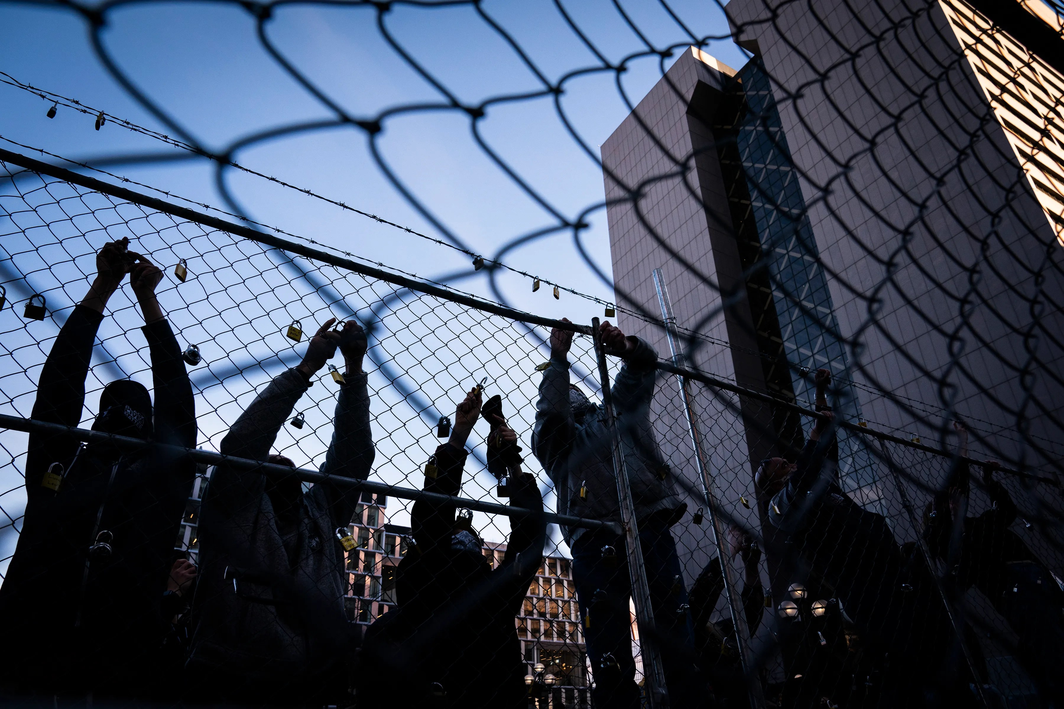 People place locks with the names of those killed by law enforcement in Minnesota on the fence outside the Hennepin County Government Center during the