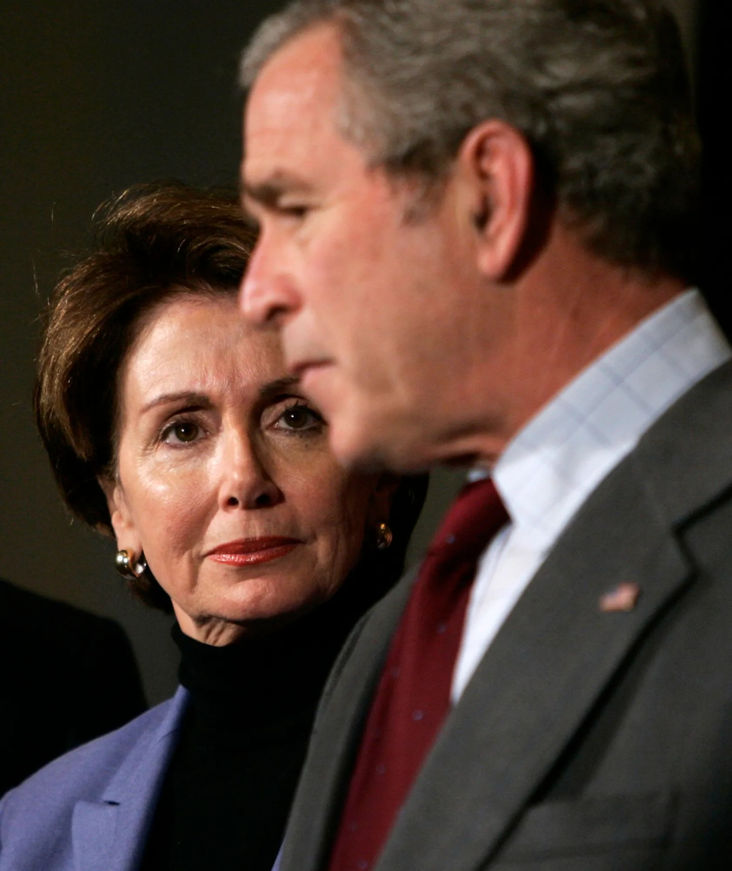 Speaker of the House Rep. Nancy Pelosi, D-Calif., left, looks on as President Bush speaks at the House Democratic Issues Conference on Feb. 3, 2007, in Williamsburg, Va.