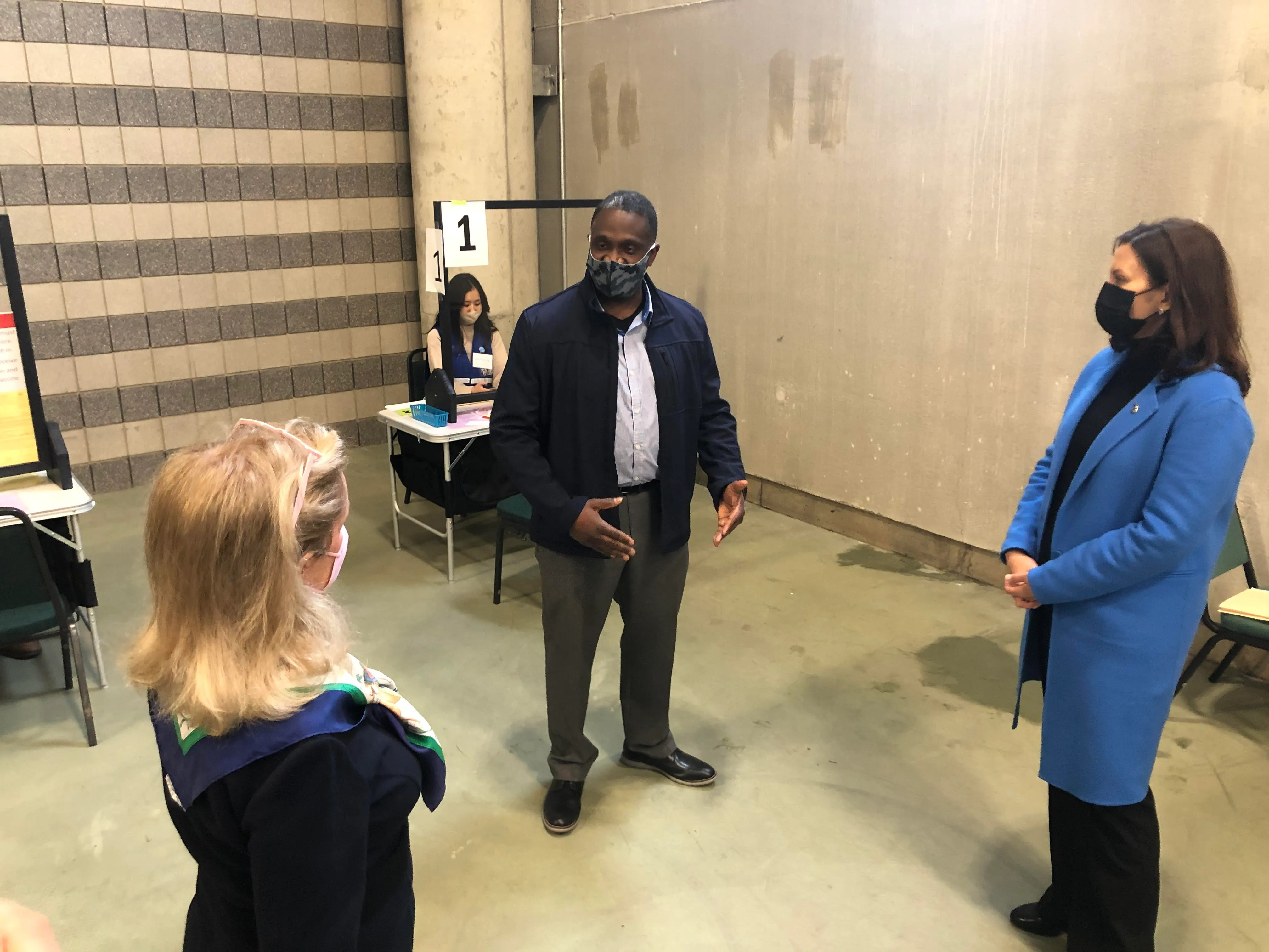 Kevin Lawson, 51 from Ypsilanti, chats with Representative Debbie Dingell and Governor Gretchen Whitmer before getting vaccinated against COVID-19 at the Eastern Michigan University convocation center on April 12, 2021.
