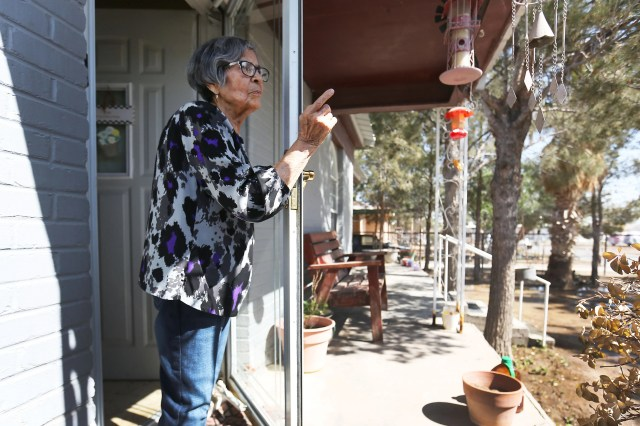 Maria Baeza Valeriano stands on her front porch talking about her neighborhood on April 9, 2021, in Pecos, Texas. Maria lives right across the street from what used to be a housing area for oil field workers. It is now being used as a migrant shelter for unaccompanied minors.