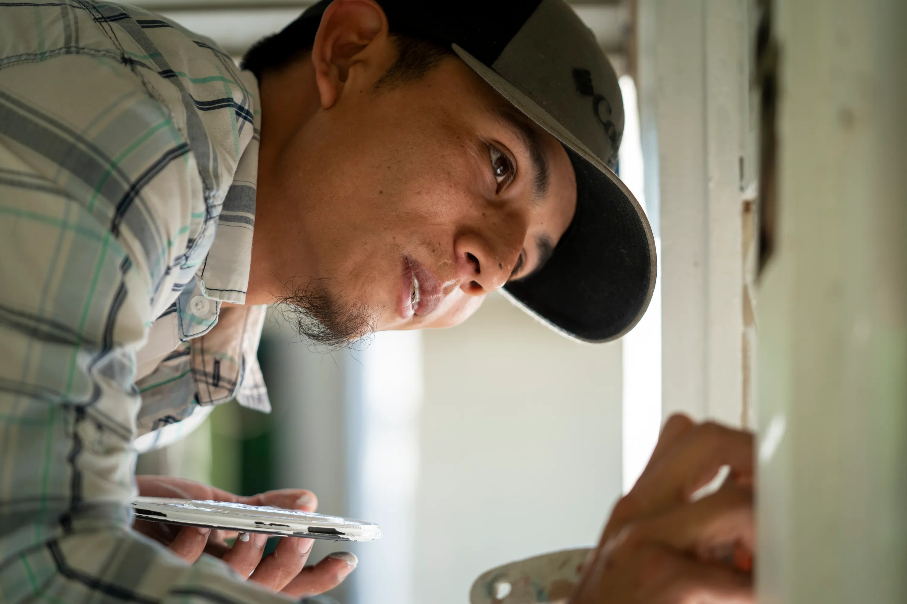 Francis Portillo paints windows at a home before an inspection in Jacksonville, Fla. on April 8, 2021.