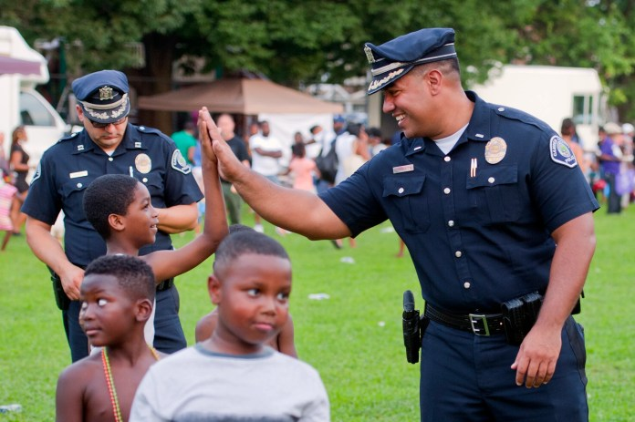 Camden County Police Chief Gabriel Rodriguez, right, high fives a member of the community. Rodriguez, a native of Camden, which is heavily Black and Latino, said crime in his city is declining in part due to repeated training sessions that encourage officers to use restraint whenever possible when interacting with citizens.