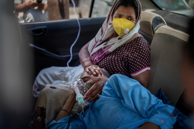 A patient breathes with the help of oxygen provided by a Gurdwara, Sikh place of worship, inside a car in New Delhi, India, Saturday, April 24, 2021.