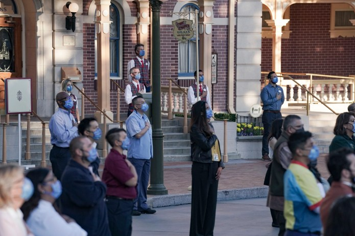 Disneyland cast Members watch as Color Guard members raise the flag inside of Disneyland.